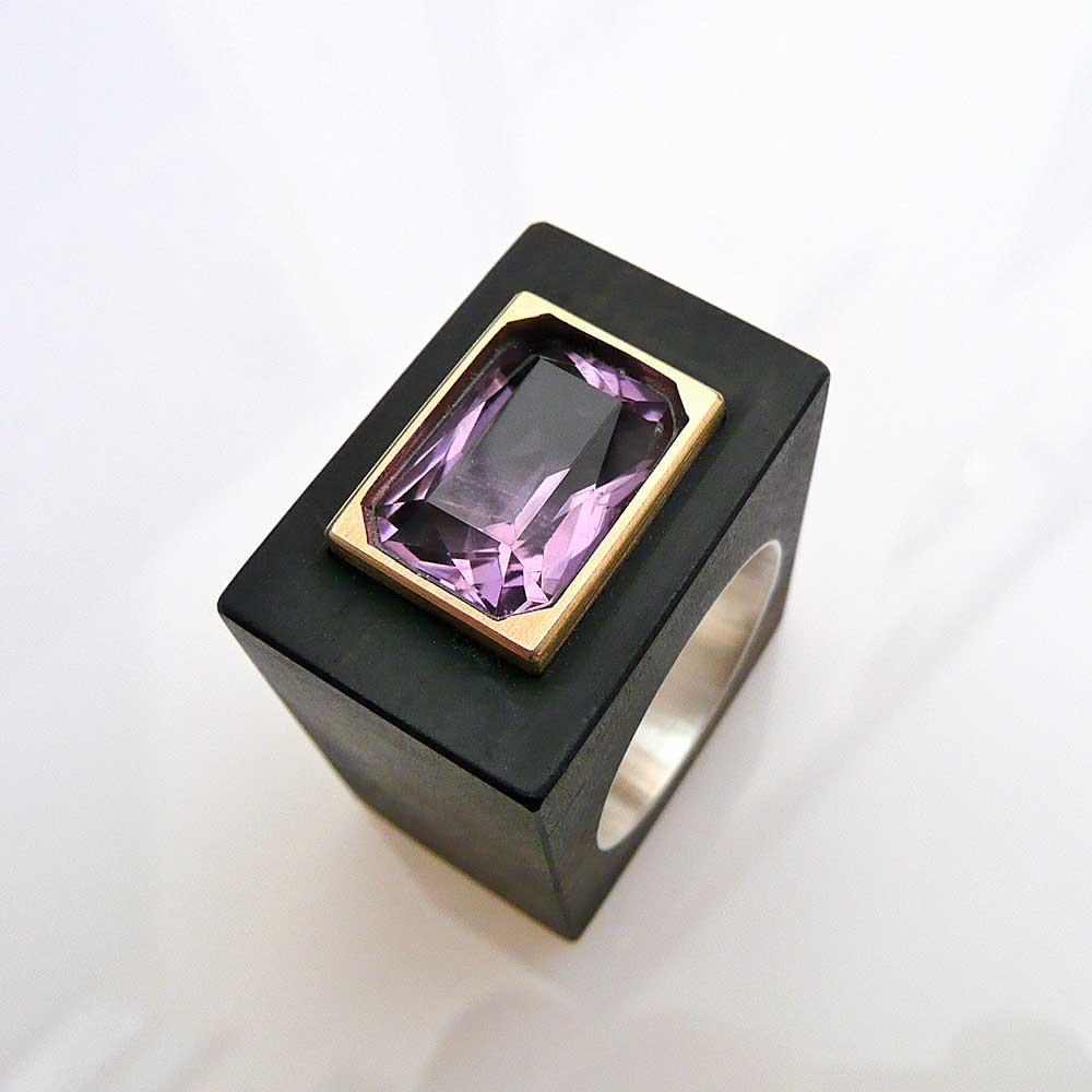 Kastenförmiger, schwarzer Ring mit lila Stein